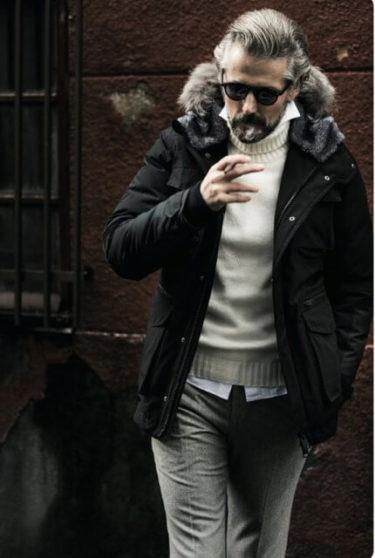 渋いオヤジがかっこいいダウンを着てタバコを吸っている