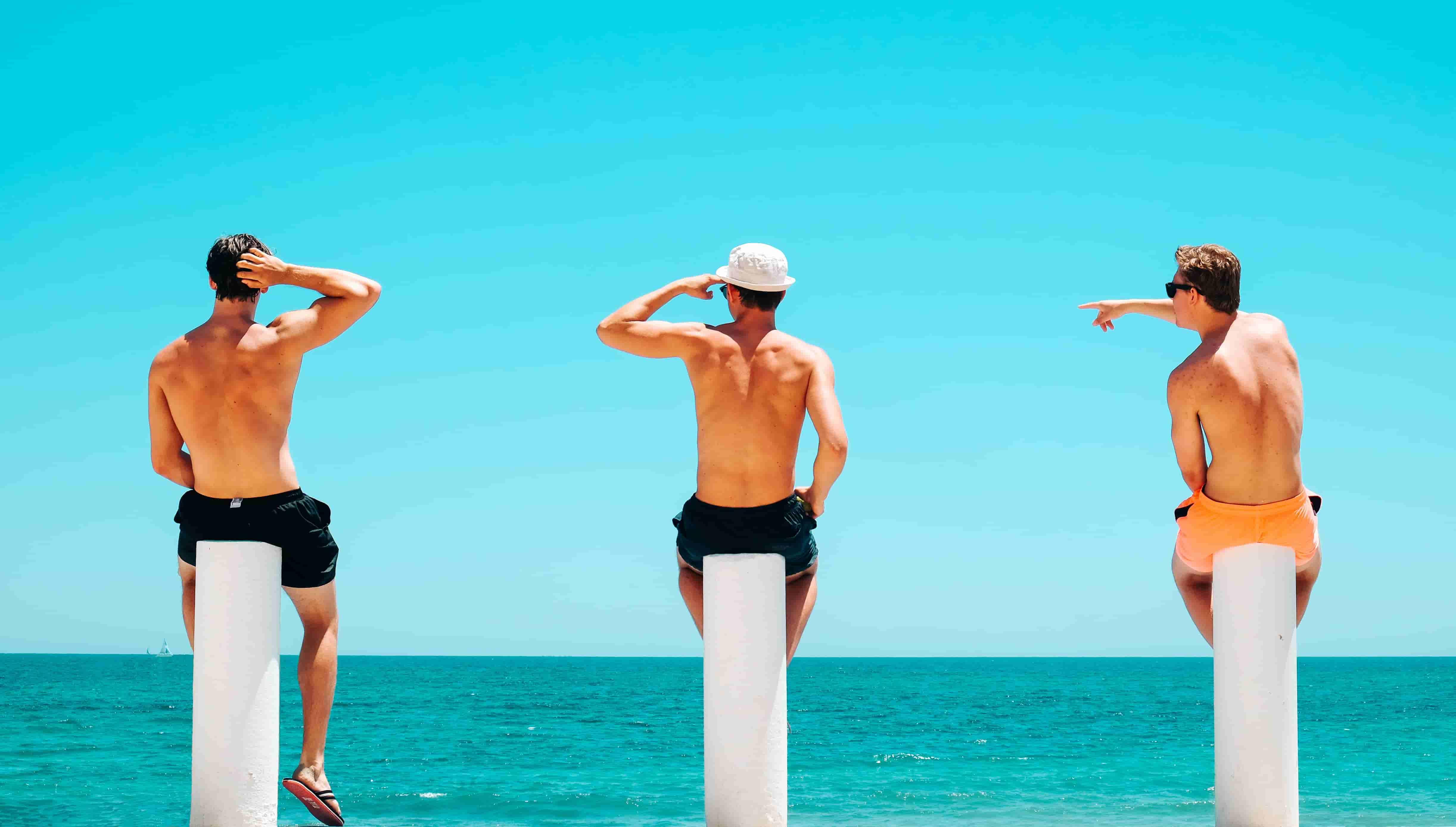 海を背にしている外人3人