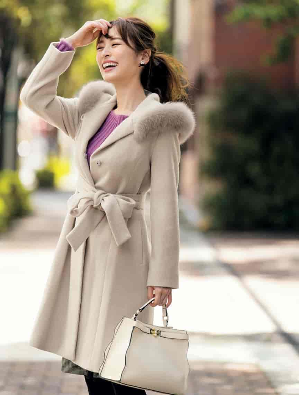 ベージュのコートを着て笑顔の美女