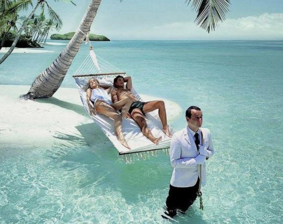 ビーチ沿いの白いハンモックに寝そべる外国人カップル